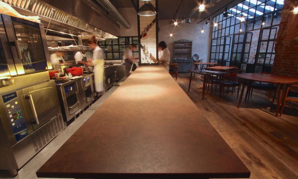 La espectacular barra-encimera de la cocina abierta a la sala, realizada en Dekton