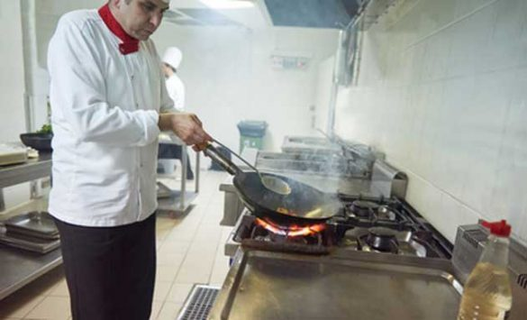 Cocinero con una sartén al fuego