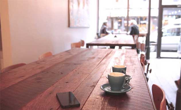 Tazas de café y móvil en una cafetería