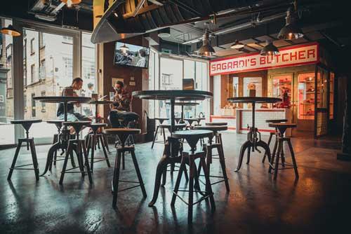 Mesas altas en la zona de bar del Sagardi de Londres; al fondo, la carnicería