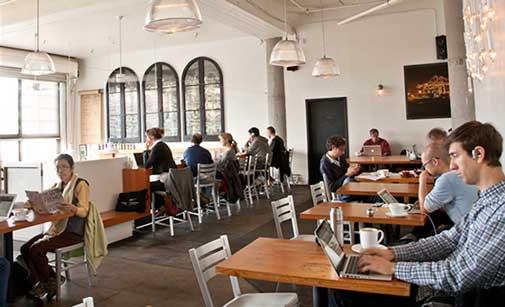 Gente conectada al wifi en una cafetería
