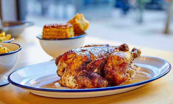 El pollo macerado y asado lentamente al carbón es la estrella de Le Coq