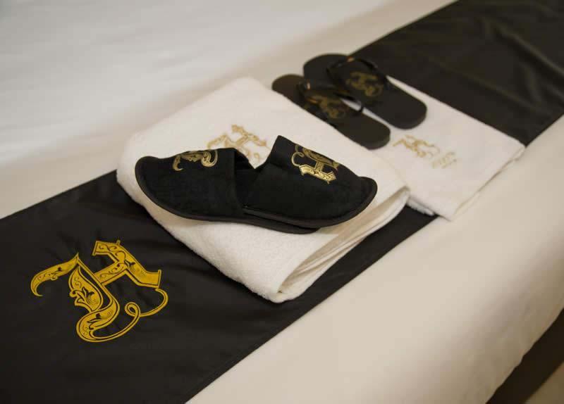 Toallas y zapatillas bordadas en el Hugo's Hotel Boutiqye