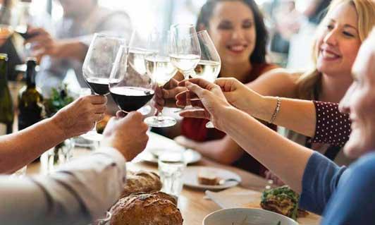 Comensales brindando en la mesa de un restaurante