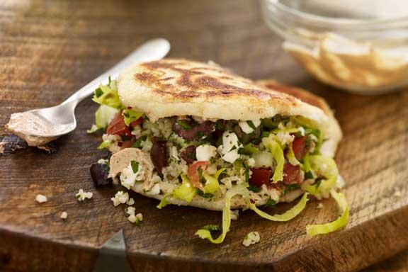 Arepa rellena de carne, verdura y salsa tzatziki