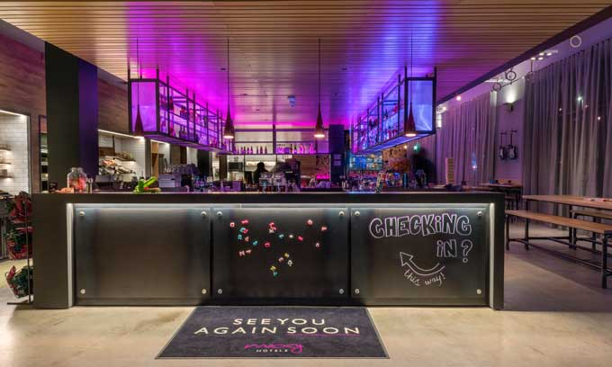 La original recepción de un hotel Moxy, concebida como la barra de un bar. Fotos de Andrew Horwitz
