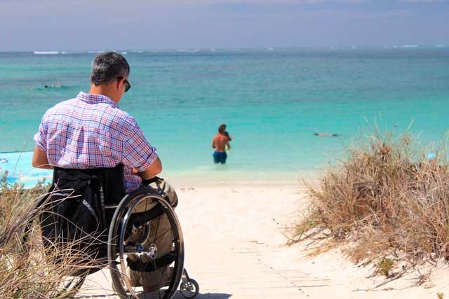 Persona con silla de ruedas en una playa