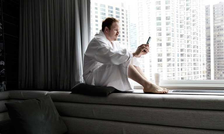 Profesionalhoreca, consultando el móvil en la habitación del hotel