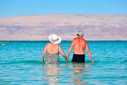 Profesionalhoreca: pareja de turistas senior en una playa