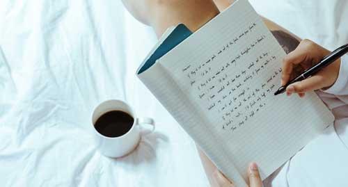 Profesionalhoreca, escribiendo con un bolígrafo en la cama de un hotel