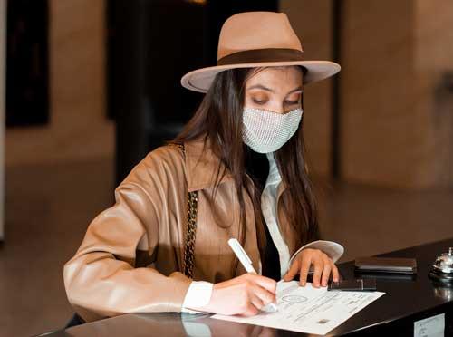 Profesionalhoreca, firmando con uno de los bolígrafos personalizados para hoteles en la recepción de un hotel